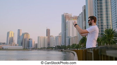 A man in the summer standing on the waterfront photographed on a smartphone landscape of the city