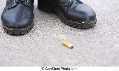 A man in torn, tattered boots on lacing stands in the middle of the street beside a cigarette butt.