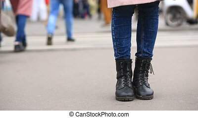 A man in torn, tattered boots on lacing stands in the middle of the street in a crowd of passers-by