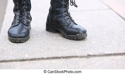 A man in torn, tattered boots on lacing stands in the middle...