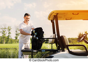 A man in white clothes stacks a bag with golf clubs on the trunk of a golf cart