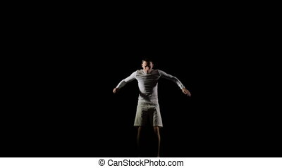 A man in white doing acrobatics on a black background in slow motion