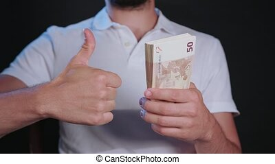 A Man in White T-Shirt Holding Cash - A man wearing a white...