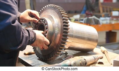 A man inserts a bearing into a large metal gear - industry...