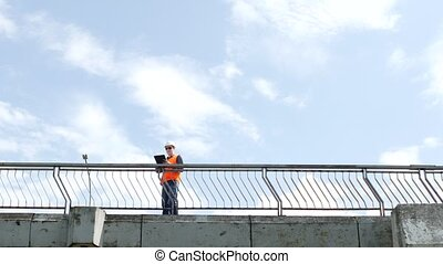 A man inspector walks across the bridge looking around and inspects the quality of the bridge, checks, engineer