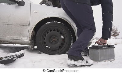 A man installs a car battery in a car, cold winter start of...