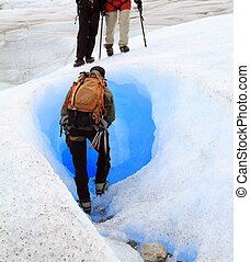 A man is about to enter to a tunnel naturally carved in a glacier in Patagonia, South America.