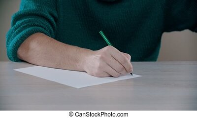 A man is actively writing word on a paper