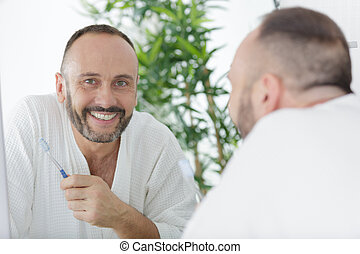 a man is brushing teeth
