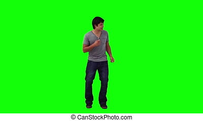A man is dancing and singing against a green background