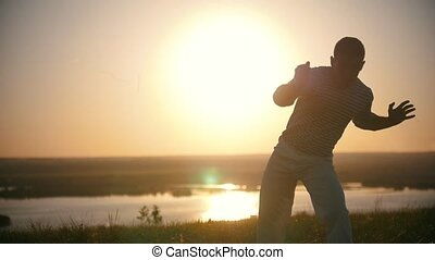 A man is engaged in capoeira, sunset, close up, slow-motion,...