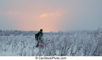 A man is engaged in skituring. A man walks against field - A...