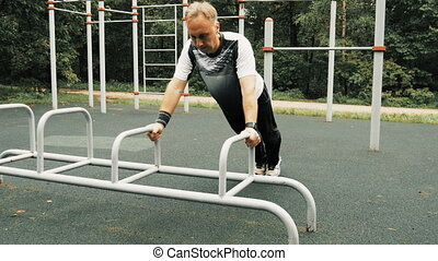 A man is exercising at an open pitch