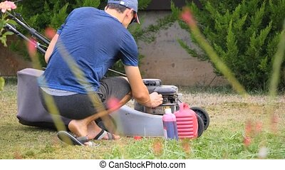 filling up the lawn mower - A man is filling up the lawn...