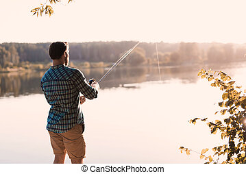 A man is fishing on the river bank. He stands with his back to the camera against the background of the river