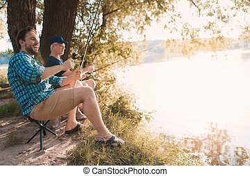 A man is fishing on the river bank with his father. They sit on folding chairs against the background of the sunrise
