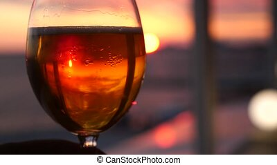 A man is holding a glass of alcohol against the sunset over the sea. close-up. Slow motion