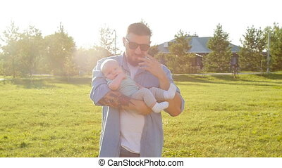 A man is holding his son in his arms outdoors