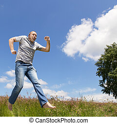 man is jumping in front of blue sky