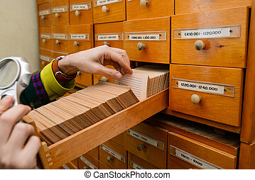 A man is looking for information in a box with paper cards. Search for data and information. Data storage in the library or in the office. Database
