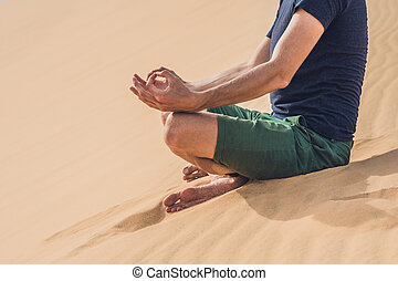 A man is meditating on the sand in the desert