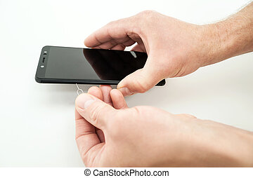 A man is opening a SIM card slot in a smartphone.