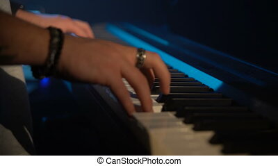 A man is playing a synthesizer. close-up
