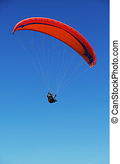 a man is playing parachute on blue sky