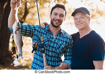 A man is posing with a fish and spinning in his hands. The old man stands next to him