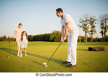 A man is preparing to strike, his wife and daughter are standing behind and looking at him