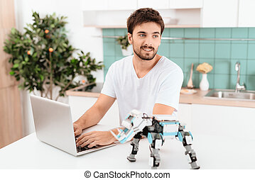 A man is programming a robot in the kitchen. He works on a gray laptop. The robot stands next to the table.