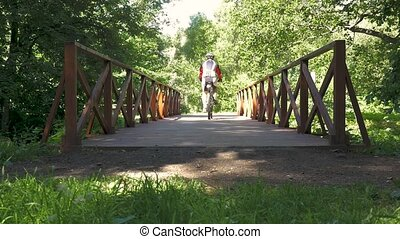 A man is riding a bicycle across the bridge in the park. slow motion