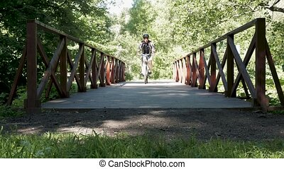 A man is riding a bicycle in the park. In summer time.