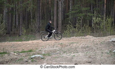 A man is riding along the forest by bike