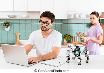 A man is sitting at the kitchen table and programming a robot. The robot is on the table. Behind the woman.