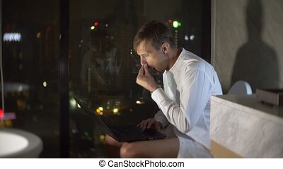 A man is sitting in the toilet in a luxurious restroom with a panoramic window at night with a laptop and works. 4k
