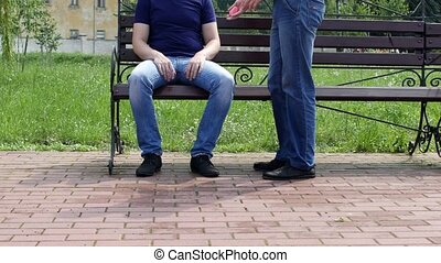 A man is sitting on a bench, another man approaches him and...