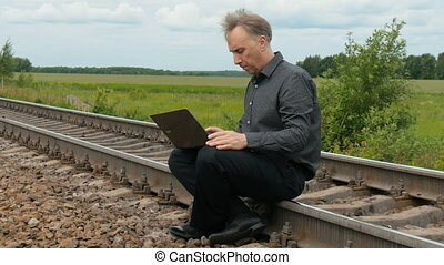 A man is sitting on the rails and working on a laptop.