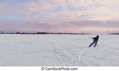 A man is skiing in the snow in a field at sunset. His...