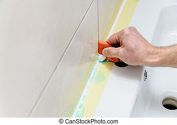 A man is smoothing the silicone sealant.