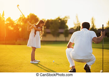 A man is squatting on a golf club and looking at a girl who is swinging a club to strike the ball