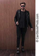 a man is standing in a black leather jacket and jeans - full...