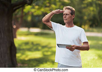 A man is standing in a park with a gray tablet in his hands. He is looking for someone