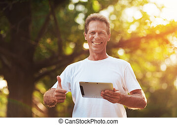 A man is standing in a park with a gray tablet in his hands. He looks at the camera and shows a thumbs up.
