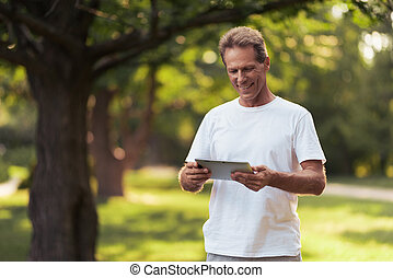 A man is standing in a park with a gray tablet in his hands. He looks at the tablet screen