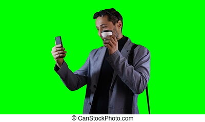A man is talking on a mobile phone in video mode. Green...