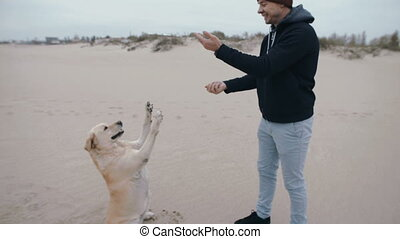 A man is training a dog and feeding it from his hand.