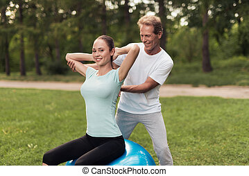 A man is training a woman doing exercises while sitting on a ball for yoga in the park