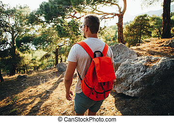 A man is traveling with a light backpack in the mountains.