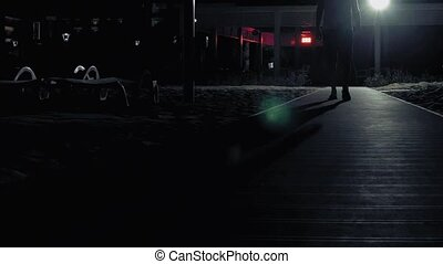 A man is walking alone in the dark on the streets